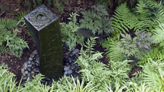 Outdoor water sculpture with ferns and rocks